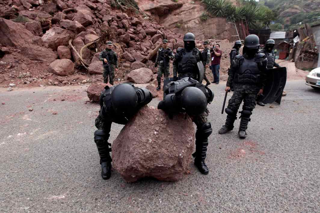 GOOD HOUSEKEEPERS: Military police remove a rock from a barricade settled by opposition supporters to block a road during a protest over a disputed presidential election in Tegucigalpa, Honduras, Reuters/UNI