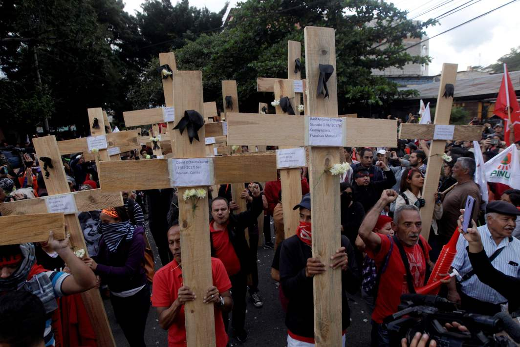 IN THEIR NAME: Opposition supporters hold wooden crosses, with the names of the victims of violence on it, during a protest over a contested presidential election with allegations of electoral fraud in Tegucigalpa, Honduras, Reuters/UNI