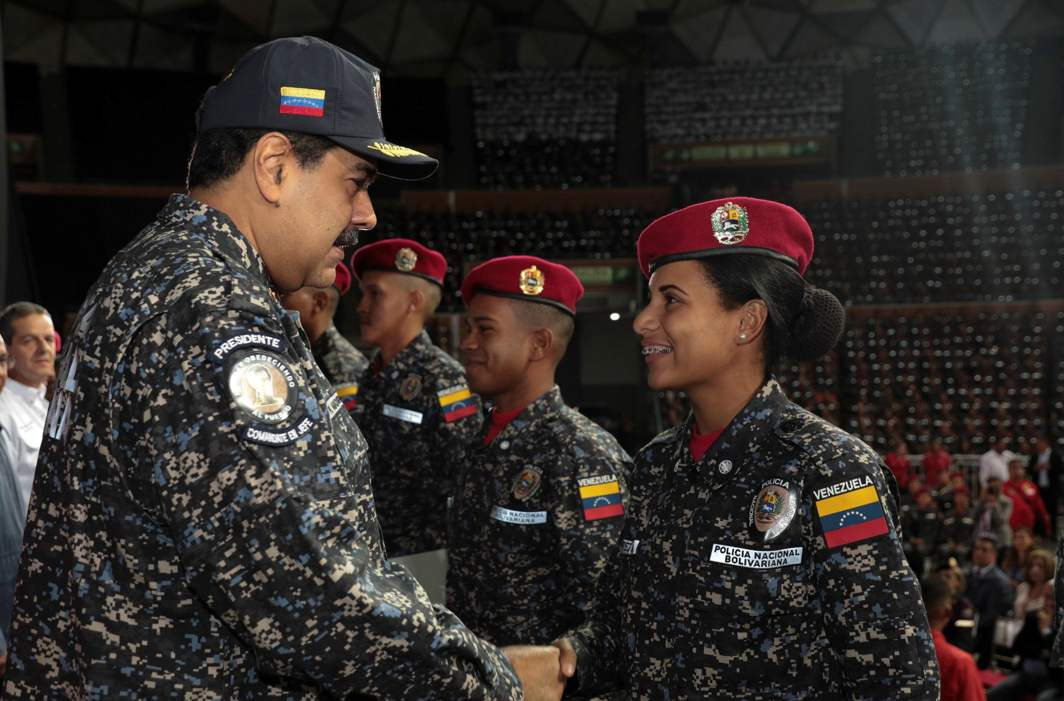 SERVE ME: Venezuela's President Nicolas Maduro (left) shakes hands with a newly graduated policewoman during a Bolivarian National Police officers' graduation ceremony in Caracas, Venezuela, Reuters/UNI