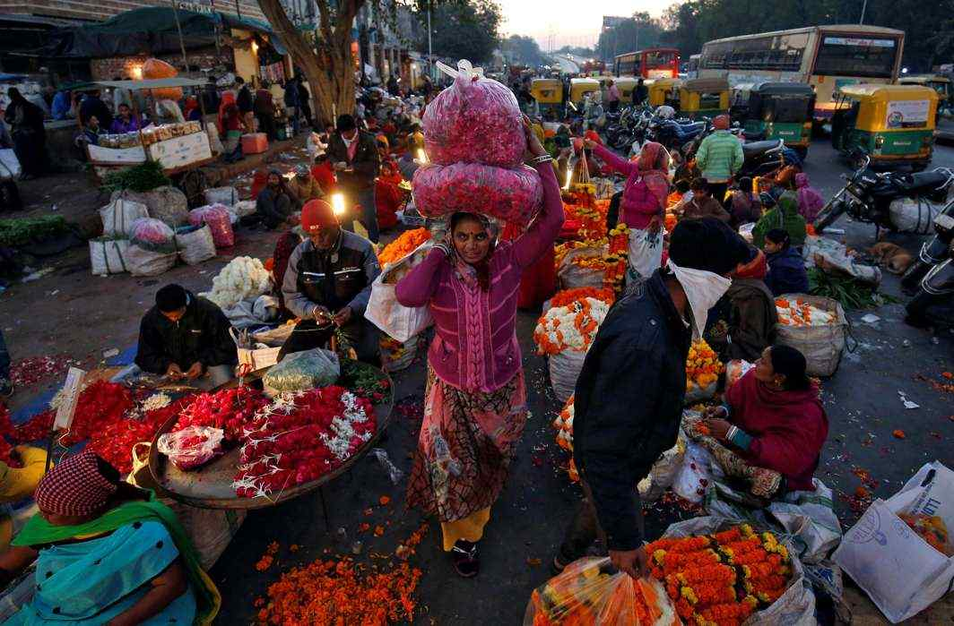 BURDEN OF ROSES: A woman carries flower garlands early morning at a wholesale flower market in Ahmedabad, Reuters/UNI