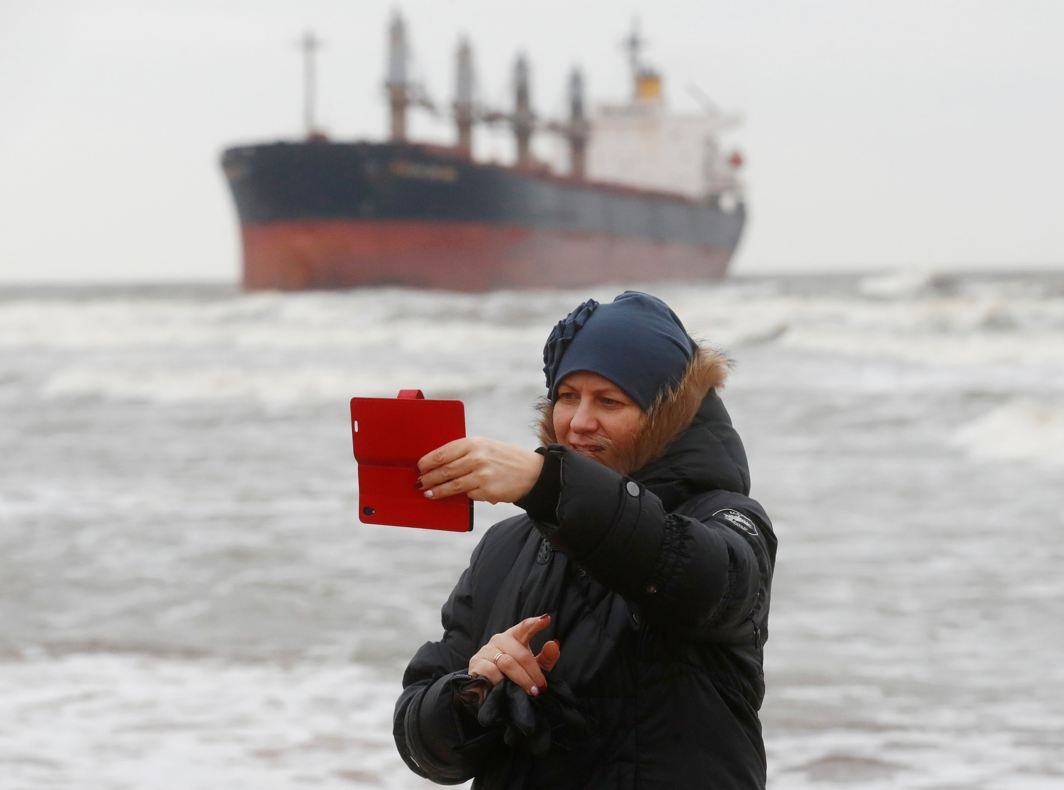 VESSEL AHOY! A woman takes a selfie in front of stranded cargo ship Ocean Crown during windy weather in Klaipeda, Lithuania, Reuters/UNI