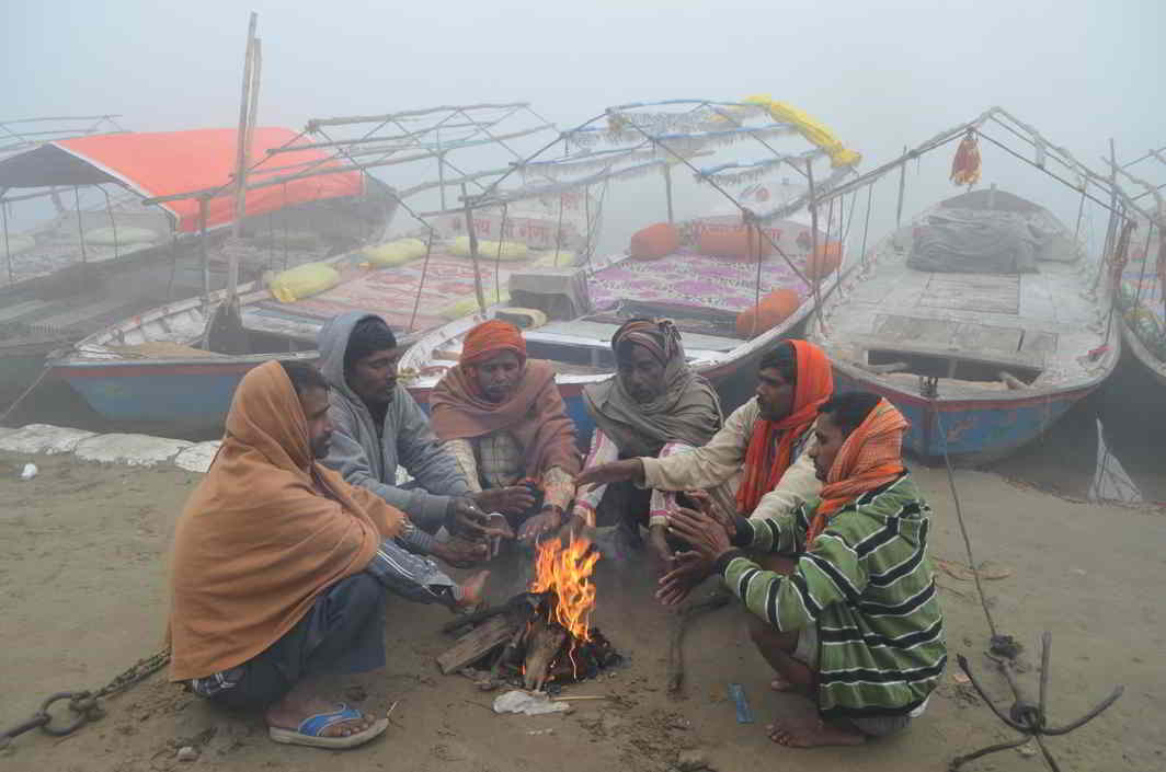 WARM UP FIRST: Boatmen wait for tourists on a foggy morning on the bank of river Ganga at Vindhyachal Dham in Mirzapur, Uttar Pradesh, UNI