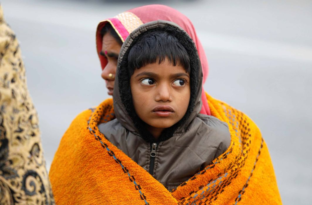 COLD COMFORT: A boy and a woman are wrapped in a single shawl as they sit at a bus terminal on a cold winter morning in New Delhi, Reuters/UNI