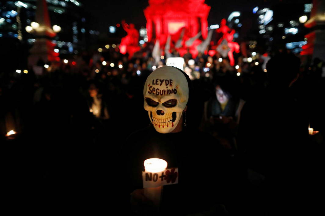 CONTROVERSIAL LAW: An activist in a mask holds a candle during a protest against a new security bill, Law of Internal Security, in Mexico City, Reuters/UNI