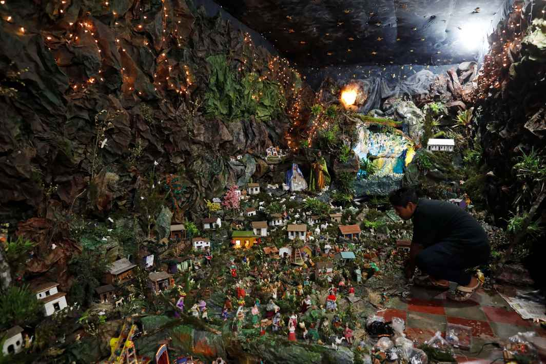 DOLLS AND HOUSES: Jeremias Ventura works on his grandmother's nativity scene with more than 2,000 figurines in Nahuizalco, El Salvador, Reuters/UNI