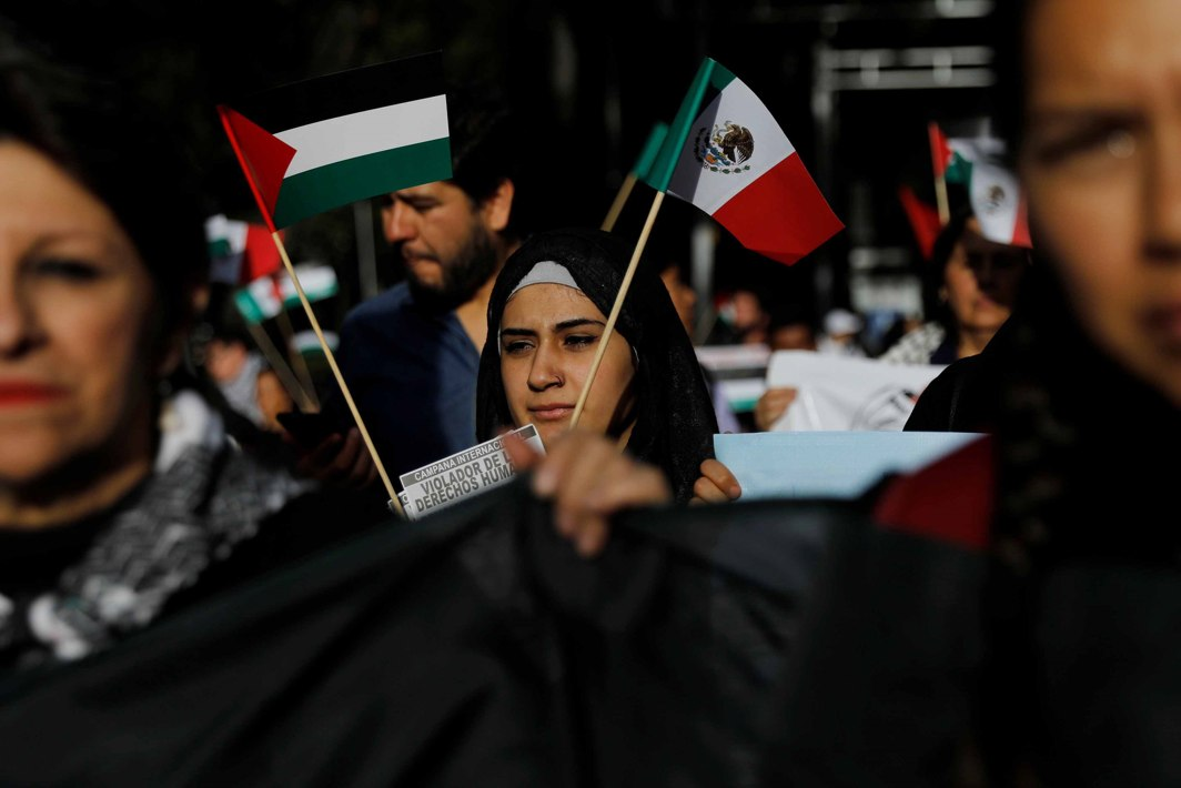 OUTRAGED: A woman holds a Palestinian and Mexican flag next to supporters of Palestine while demonstrating against Donald Trump's recognition of Jerusalem as Israel's capital, outside the US embassy in Mexico City, Reuters/UNI