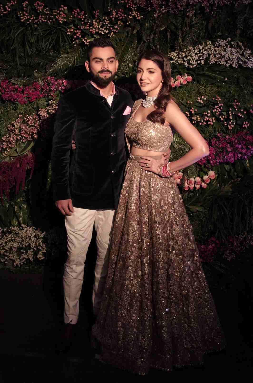 FIRST COUPLE: Indian cricket captain Virat Kohli with wife actress Anushka Sharma poses for photographers during their wedding reception in Mumbai, UNI