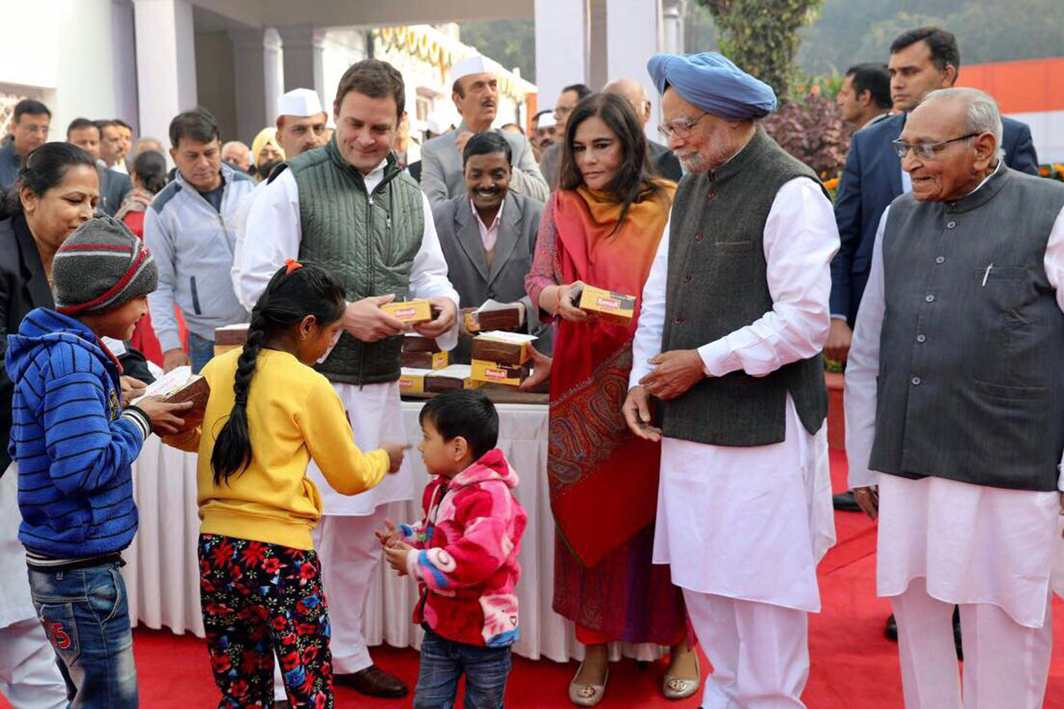 HAPPY DAY: Congress president Rahul Gandhi distributes sweets to children during the party's 133rd foundation day at AICC headquarters in New Delhi, UNI