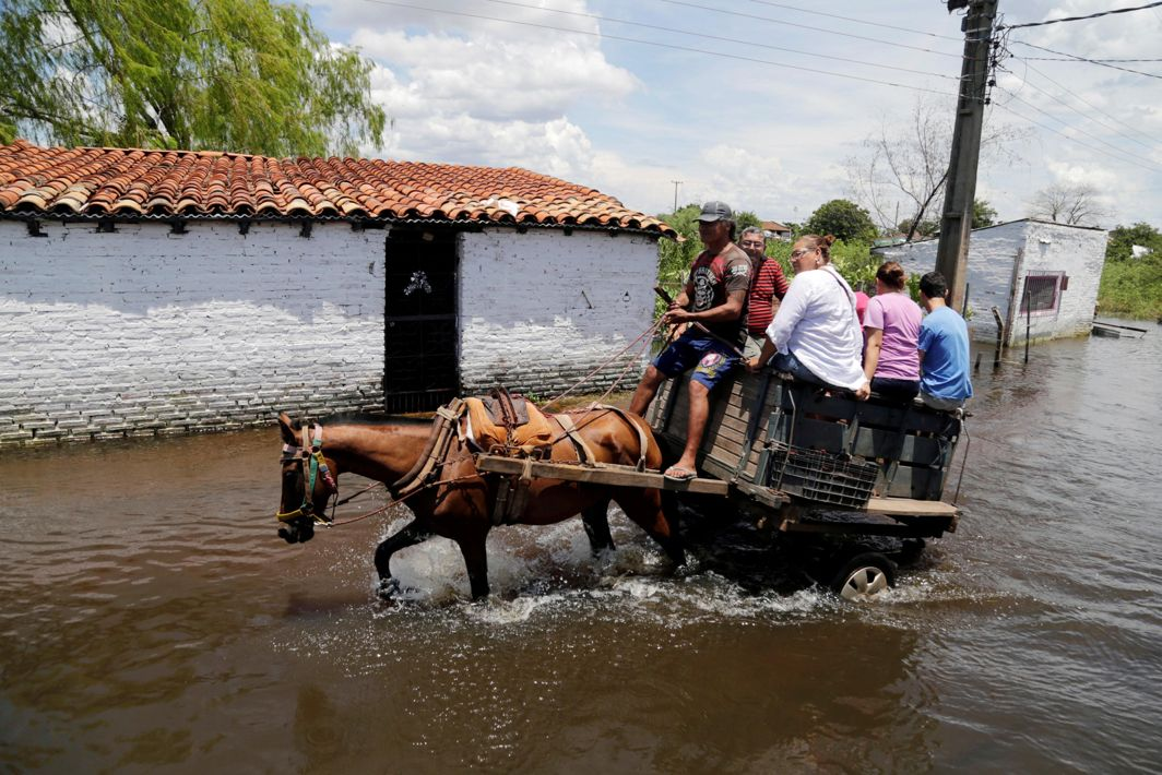 UNDER WATER: People ride on a horse carriage through a flooded street after heavy rains caused the river Paraguay to overflow, in Asuncion, Paraguay, Reuters/UNI