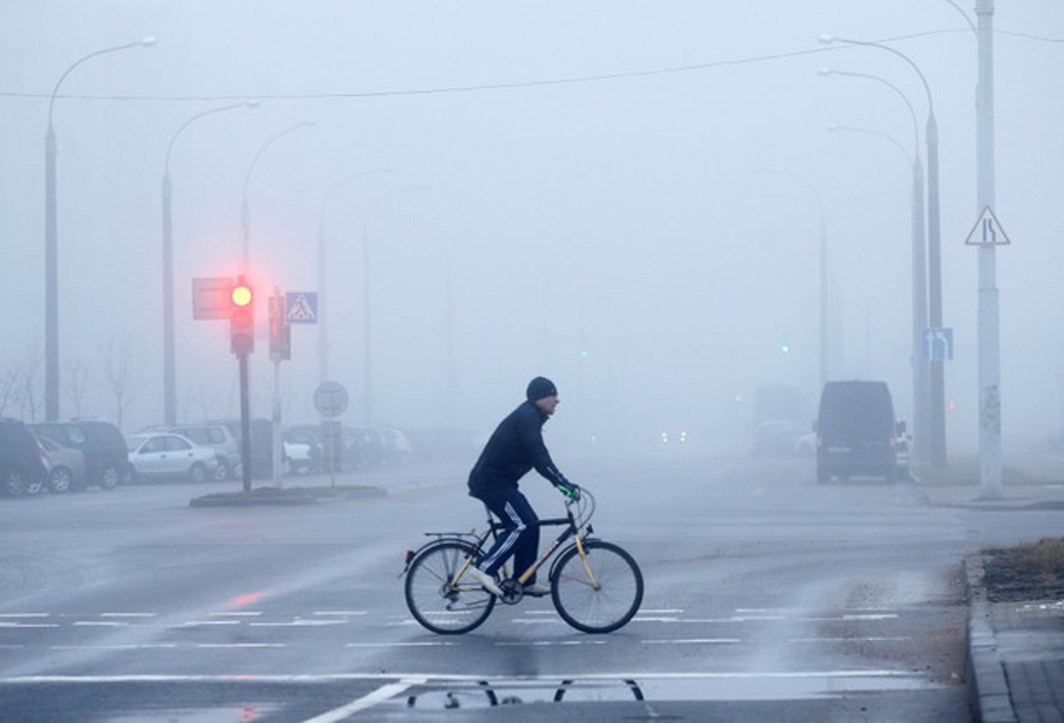 HARD TO SEE: A man rides a bicycle during heavy fog in Minsk, Belarus, Reuters/UNI