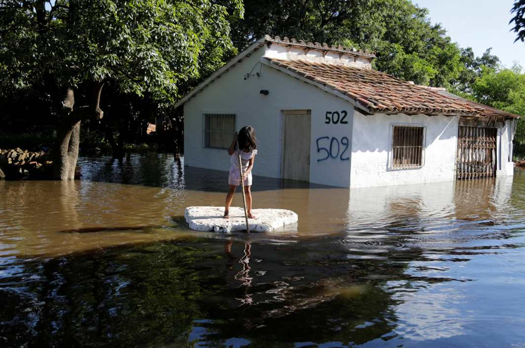 WET MISERY: A young girl uses a piece of styrofoam as a paddle board next to a flooded home after heavy rains caused the river Paraguay to overflow, on the outskirts of Asuncion, Reuters/UNI