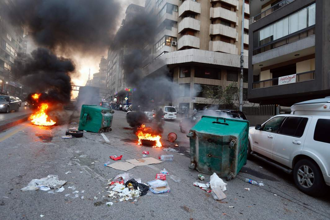 AMID THE UNREST: Cars pass burning tires in Beirut, Lebanon, Reuters/UNI