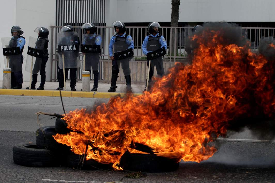 UNSATISFACTORY: Riot police guard the entrance of Honduras Central Bank as supporters of opposition candidate Salvador Nasralla burn tyres during a march to protest the results of Honduras' general elections in Tegucigalpa, Reuters/UNI