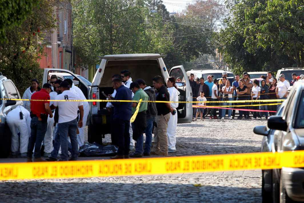 NO ENTRY WITHOUT PERMISSION: People look at forensic technicians working at a crime scene where three men were gunned down by unknown assailants, according to local media, in the municipality of Tlaquepaque, on the outskirts of Guadalajara, Mexico, Reuters/UNI