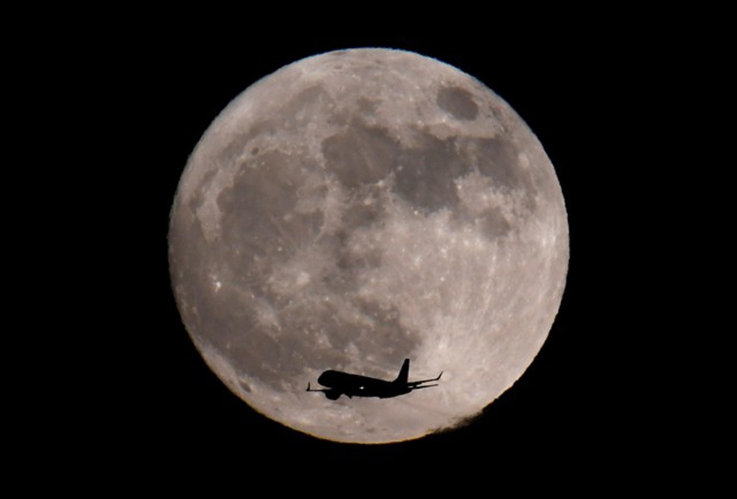 FLY IN: A passenger plane, with a 'supermoon' seen behind, makes its final landing approach towards Heathrow Airport in London, Britain, Reuters/UNI