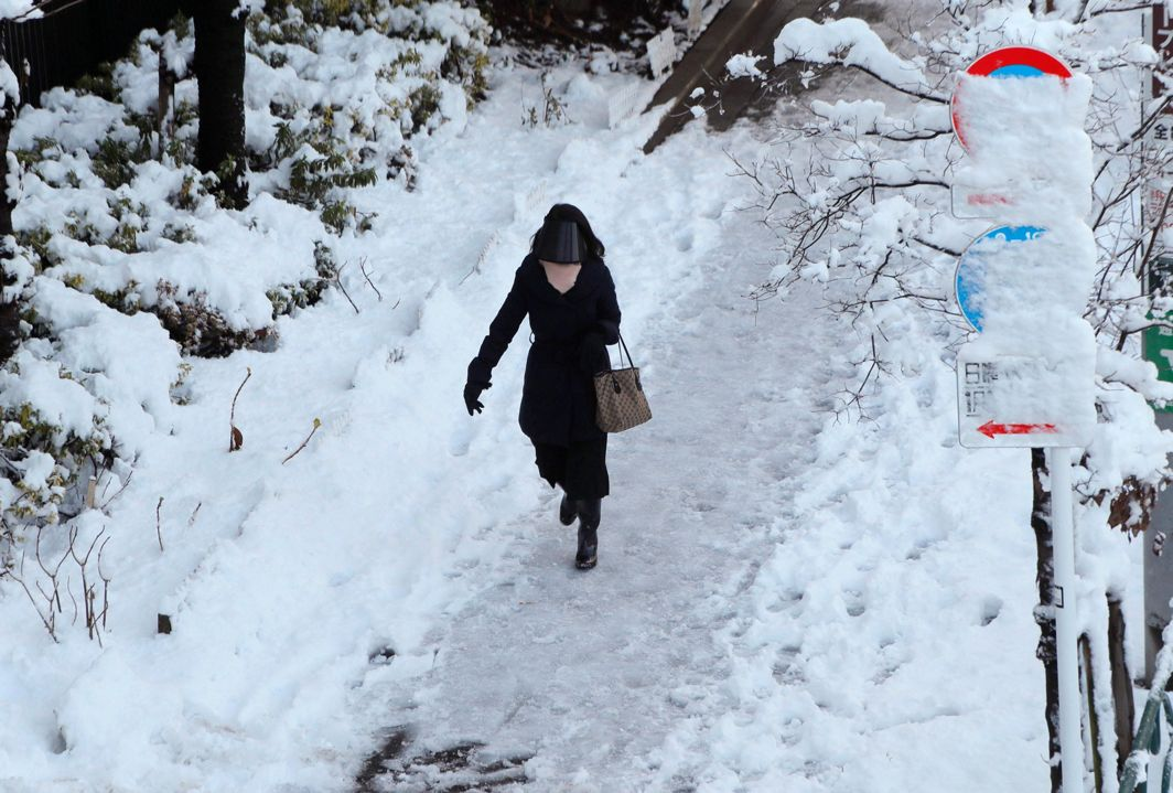 WHITE JAN: A woman makes her way on a snow-covered sidewalk in Tokyo, Japan, Reuters/UNI