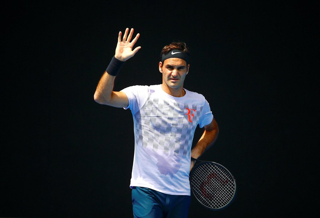 GREAT EXPECTATIONS: Roger Federer waves to his playing partner during a practice session ahead of the Australian Open tennis tournament in Melbourne Park, Reuters/UNI