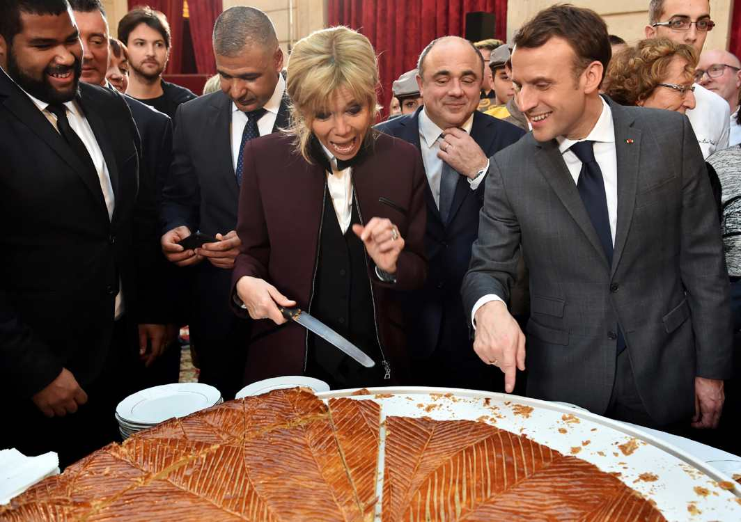 CAKE OF THE KINGS: French President Emmanuel Macron and his wife Brigitte Macron cut slices of a traditional epiphany cake during a ceremony at the Elysee Palace in Paris, France,Reuters/UNI