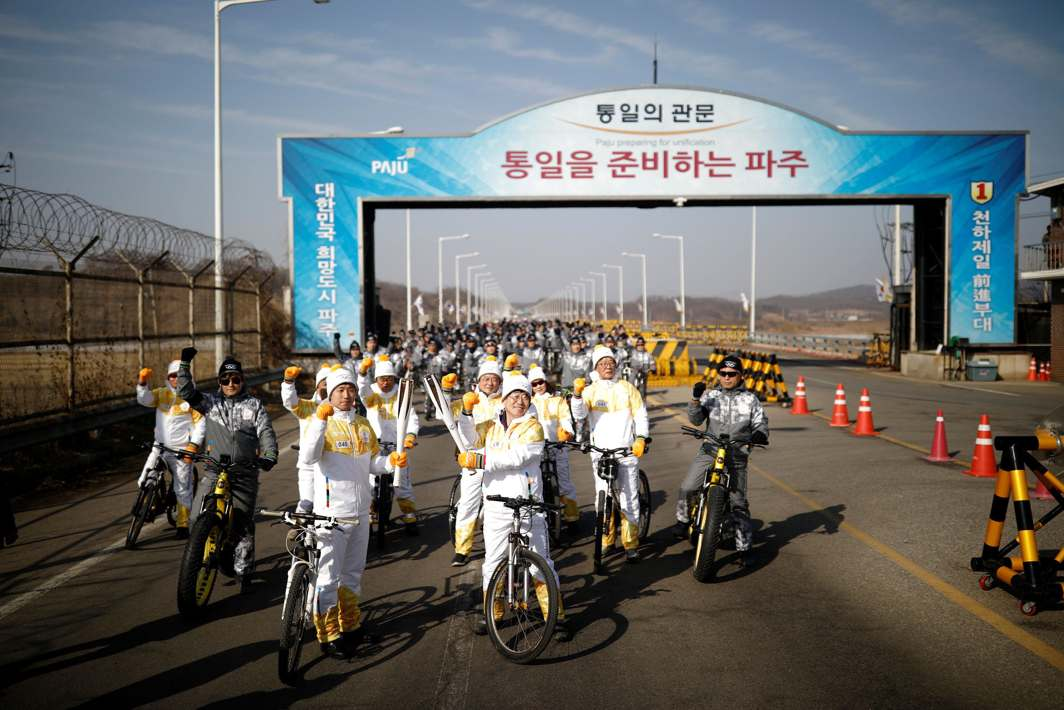 PEACE RIDE: Torchbearers pose for photographs as they participate in the Olympic torch relay on the Grand Unification Bridge which leads to the truce village Panmunjom, just south of the demilitarised zone separating the two Koreas, in Paju, South Korea, Reuters/UNI
