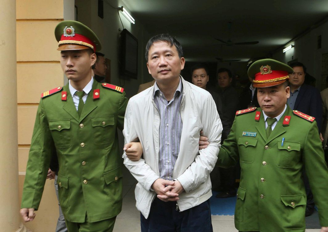 JAILED FOR LIFE: PVC's former chairman Trinh Xuan Thanh is escorted by police officers from a court to prison after verdict session in Hanoi, Doan Tan/VNA/Reuters/UNI
