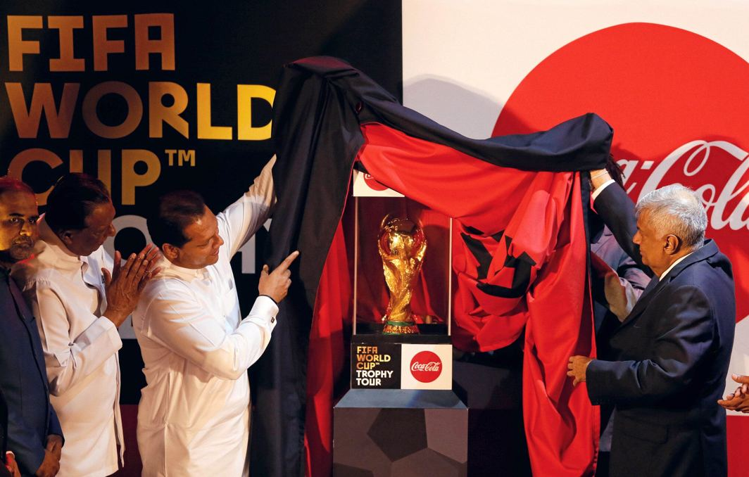 HIGH AMBITION: Sri Lankan Prime Minister Ranil Wickremesinghe (R) and Sports Minister Dayasiri Jayasekara (2nd L) unveil the FIFA World Cup trophy which starts a 50-country global tour from the Sri Lankan capital at a ceremony in Colombo, Sri Lanka, Reuters/UNI
