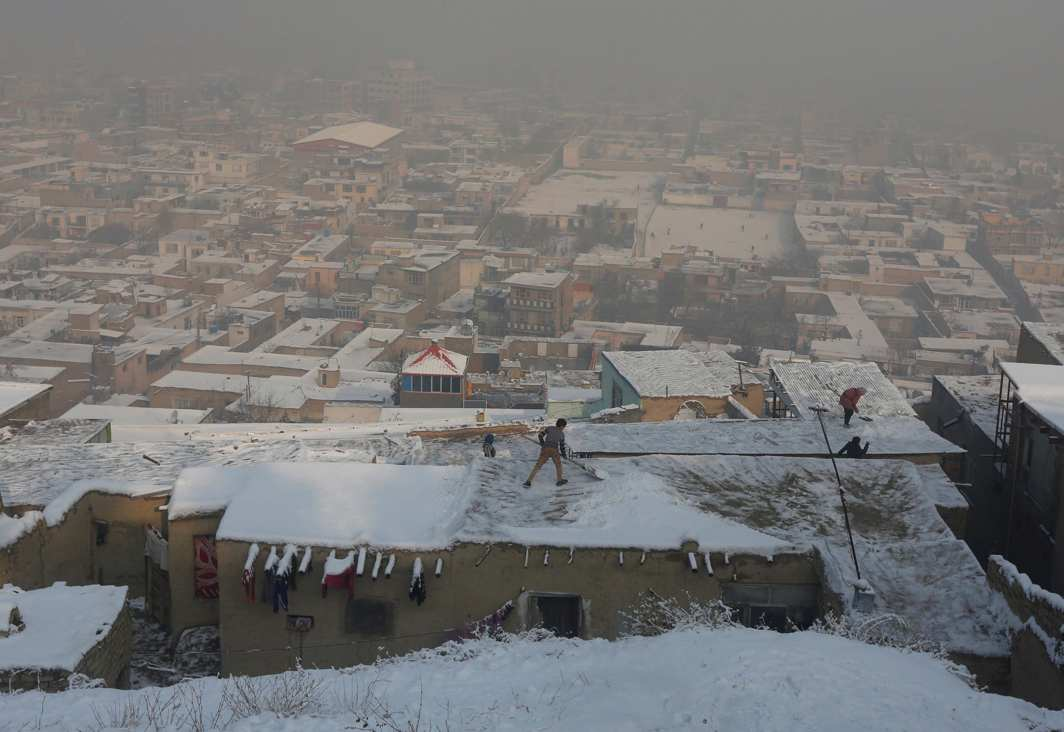 AGAINST THE ELEMENTS: An Afghan boy shovels snow from the roof of houses in Kabul, Afghanistan, Reuters/UNI
