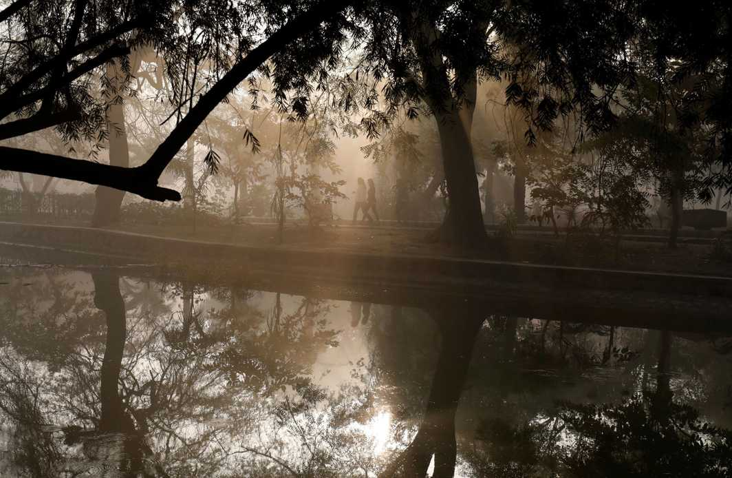 SERENDIPITY: People walk by a lake at a public park on a foggy winter morning in New Delhi, Reuters/UNI
