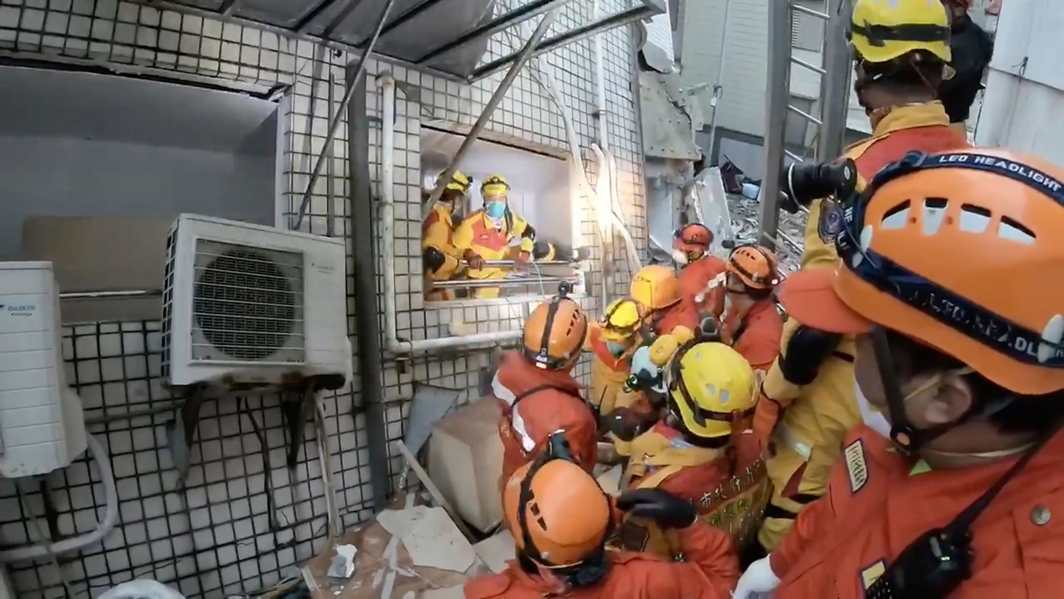 CAREFULLY LEAVE: Rescuers evacuate a building due to an aftershock in Hualien, Taiwan, Reuters/UNI