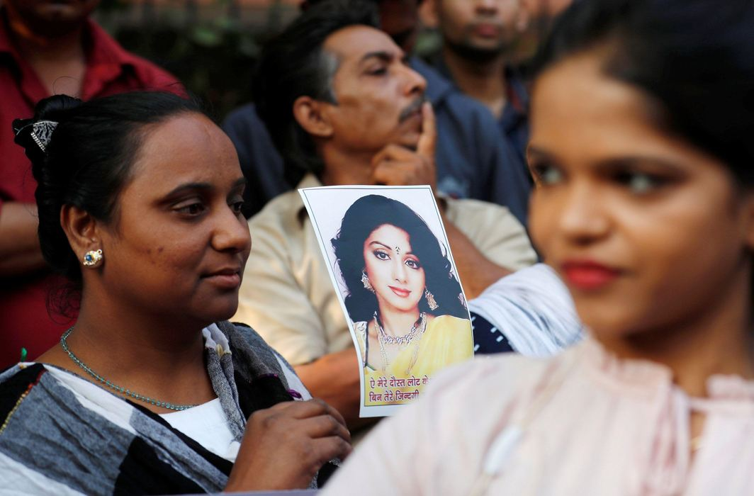 DIVA IN THE SKY: Fans of of Bollywood actress Sridevi hold her portrait as they wait to offer their condolences outside a makeshift memorial in Mumbai, India, Reuters/UNI