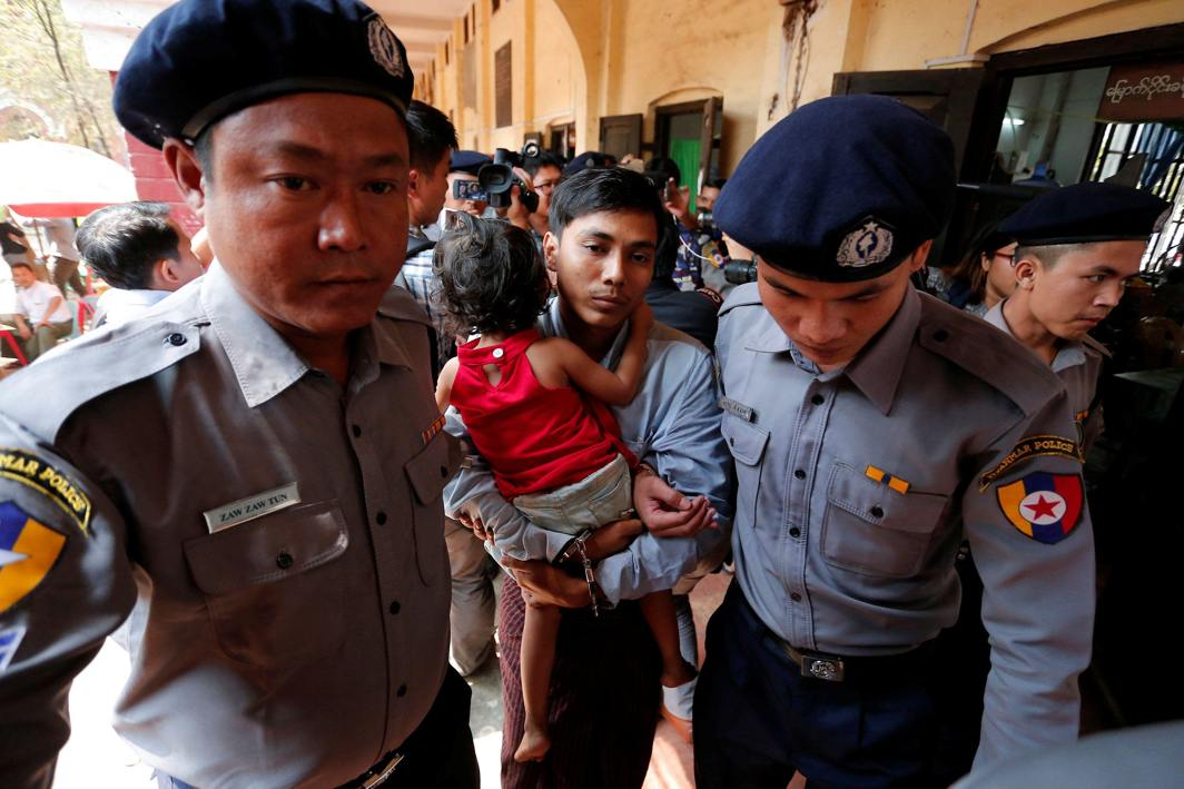 FAMILY TIME: Detained Reuters journalist Kyaw Soe Oo is escorted by police as he carries his daughter during a lunch break at a court hearing in Yangon, Myanmar, Reuters/UNI