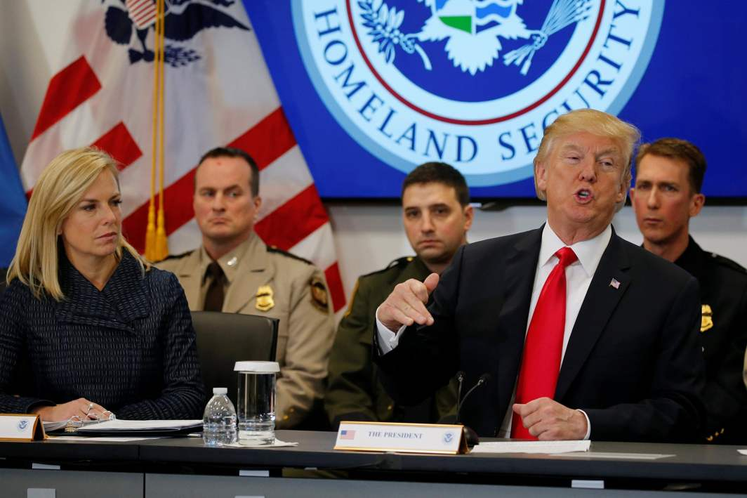SETTING POLICY: President Donald Trump, flanked by Secretary of Homeland Security Kirstjen Nielsen (L), holds a meeting at the US Customs and Border Protection's National Targeting Center in Sterling, Virginia, Reuters/UNI