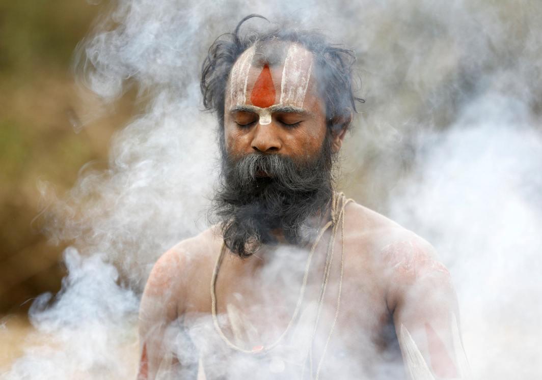 HAIL THE FATHER: Smoke rises as a Hindu holy man, or sadhu, perform religious rituals at the premises of Pashupatinath Temple during the Shivaratri festival in Kathmandu, Nepal, Reuters/UNI