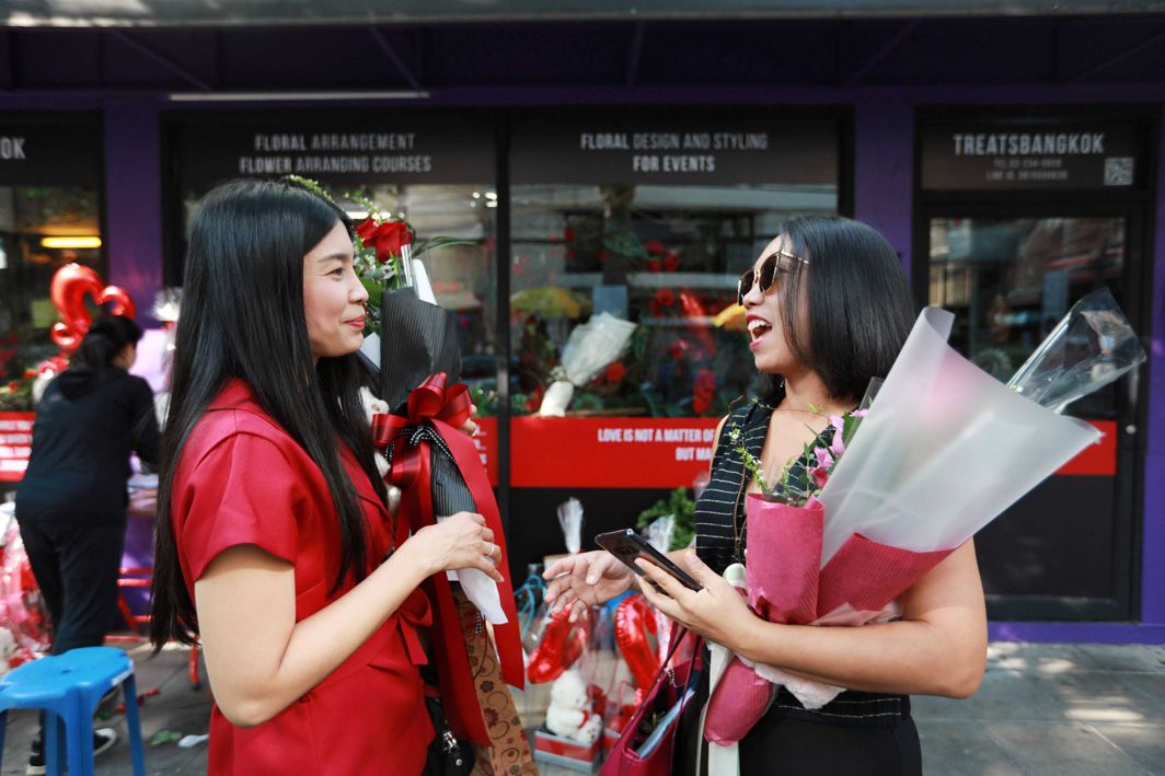 HAPPY DAY: Women chat as they hold flowers during a Valentine's Day celebration in front of a gift shop in Bangkok, Thailand, Reuters/UNI