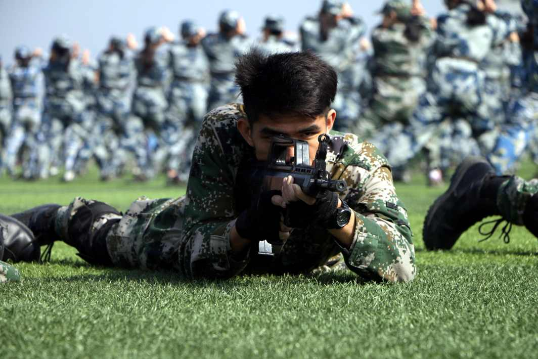HELLUVA TIME: Students take part in a military training with replica guns at the business school of a university campus in Hangzhou, Zhejiang province, China, Reuters/UNI
