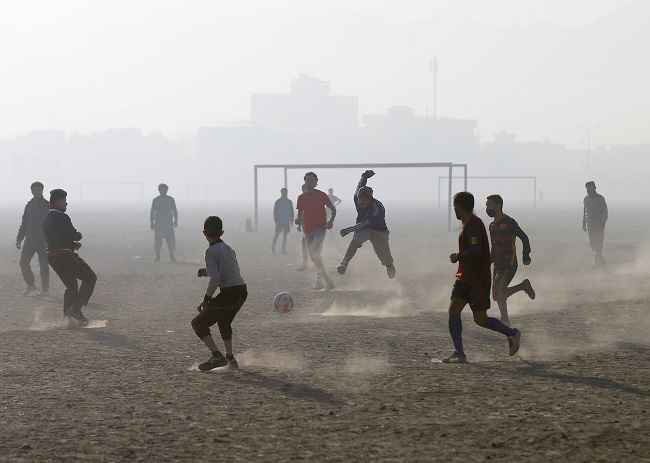 KABUL, DEC 28 :- Afghan youth play football during a foggy morning in Kabul, Afghanistan December 28, 2016. REUTERS-13R