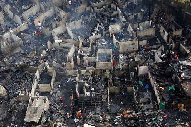 MANILA, DEC 28 :- Residents sift through the ruins of their houses after a fire razed a squatter colony, in Quezon city, Metro Manila in the Philippines December 28, 2016. REUTERS-1R