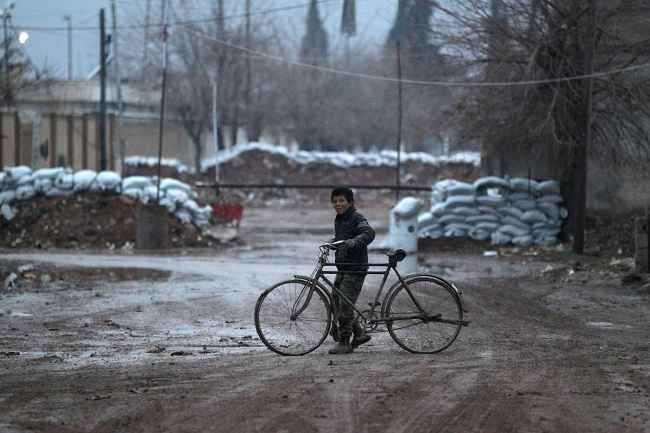 ALEPPO, DEC 28:- A boy walks his bike near stacked sandbags in al-Rai town, northern Aleppo province, Syria December 27, 2016. REUTERS-6R