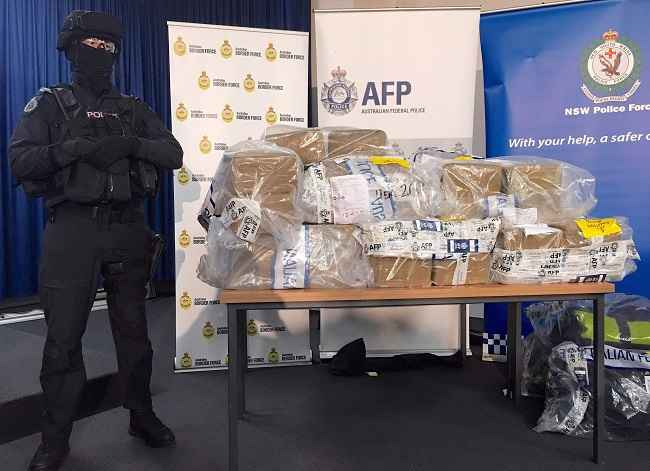 SYDNEY, DEC 29:- An armed Australian Federal Police (AFP) officer stands next to the seized shipment of around 1.1 tonnes of cocaine during a media conference in Sydney, Australia, December 29, 2016 which they say has an estimated street value of around A$360 million (US$300 million). REUTERS-4R